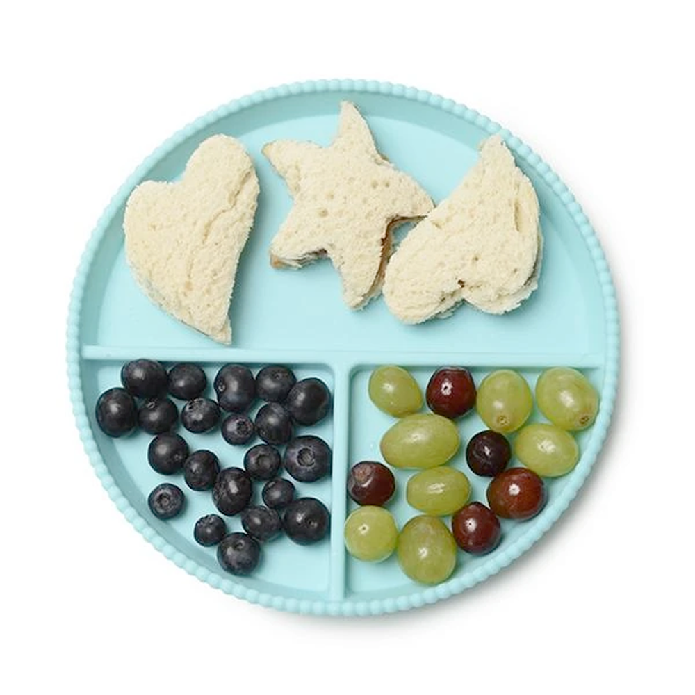 Chewbeads Silicone Plate in Turquoise with blueberries, grapes, and cookie-cutter sandwiches on it