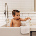 Child in sink bath playing with Oli & Carol soap