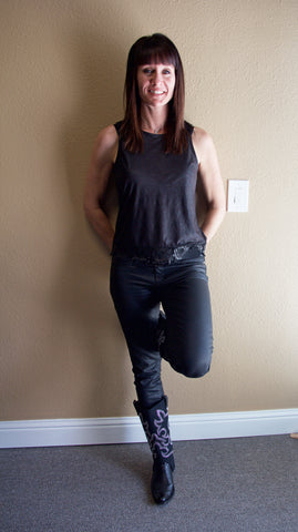 Brunette woman wearing a black shirt and black pants with cowboy boots