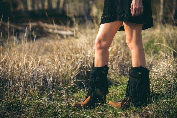 girl in a field wearing black fringe cowgirl boots
