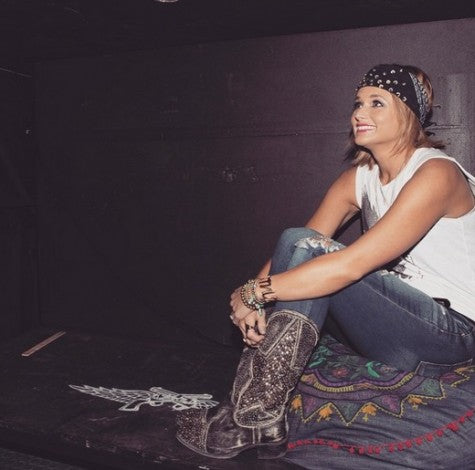 Miranda Lambert wearing ripped jeans, a white shirt and cowboy boots