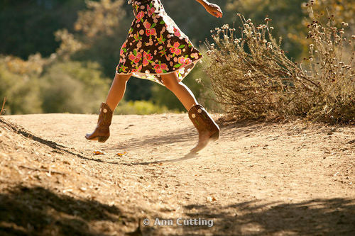 a girl in a floral dress wearing cowboy boots running on the dirt