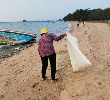 woman cleaning plastic from a beach