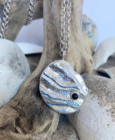 """Close up of new 'Ripples"""" pendant in sterling silver, with bezel set onyx cabochon, from the new """"Shoreline"""" collection"""