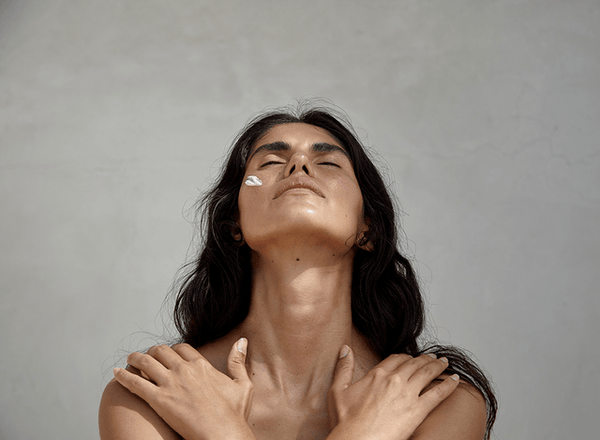 Image of topless womxn closing her eyes with face cream on and arms across chest.