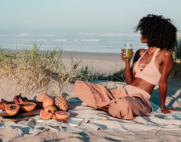 A womxn of color having a beach picnic with fresh fruits and a green juice in hand.