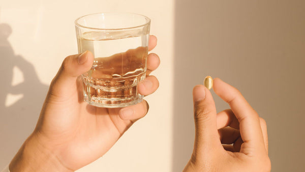 Two hands holding a glass of water and an oil capsule.