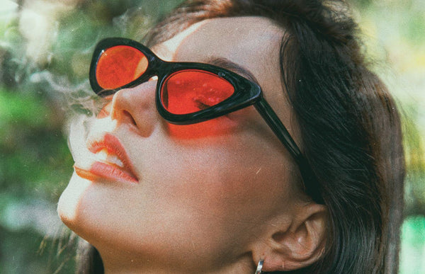A young woman with sunglasses on, looking up while exhaling smoke.