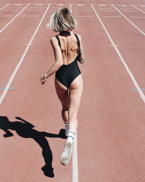 woman running on a track in a bathing suit