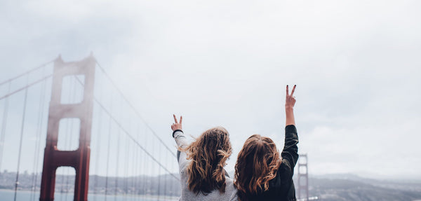 Two young women standing in front of the Golden Gate Bridge.