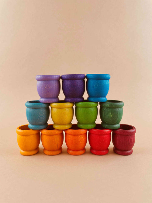 A set of 12 wooden mates, or toy cups, in rainbow colors and stacked in a display. Five cups on the bottom row (dark red to orange), 4 in the middle row (green to light blue), and three on the top row (blue to violet).