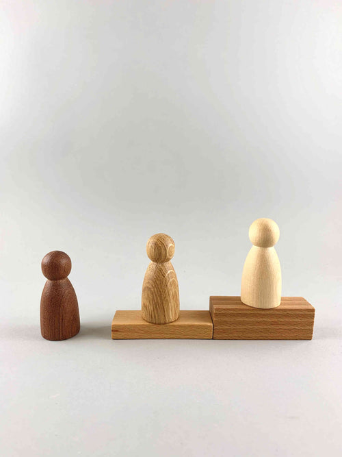 Three wooden peg figure toys in three different natural wood tones from dark to light, placed on wooden blocks in the shape of stairs.