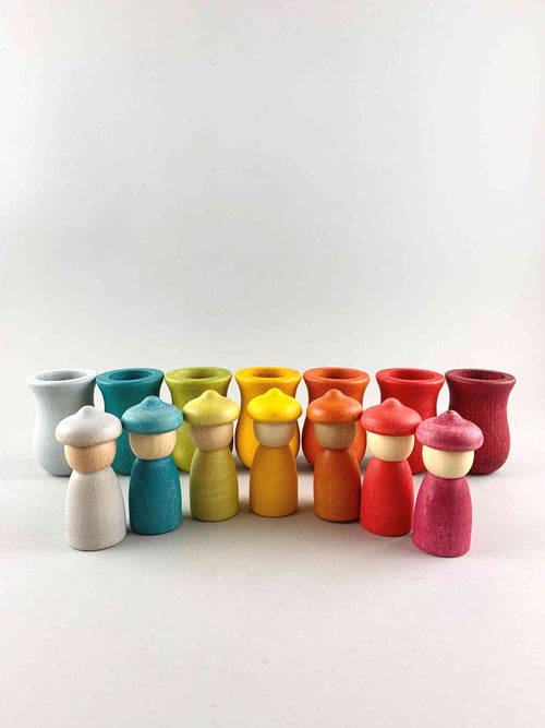 Seven rainbow color Grapat Weekly Calendar cups and Nins wooden toy figures placed in separate rows.