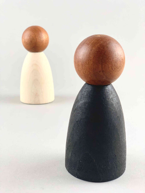 Two oversized dark wood tone Grapat Nins wooden toy figures in black (foreground) and white (background).