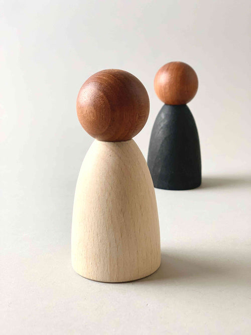 Two oversized dark wood tone Grapat Nins wooden toy figures in white (foreground) and black (background).