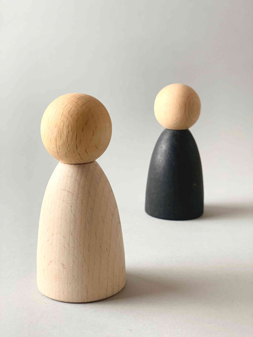 Two oversized light wood tone Grapat Nins wooden toy figures in white (foreground) and black (background).