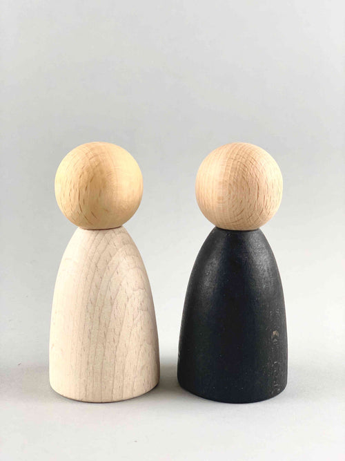 Two oversized light wood tone Grapat Nins wooden toy figures in black and white placed adjacent to each other.