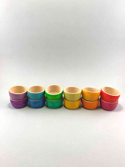 A set of rainbow colored wooden bowls nested inside each other. Six stacks of two bowls in matching color hues.