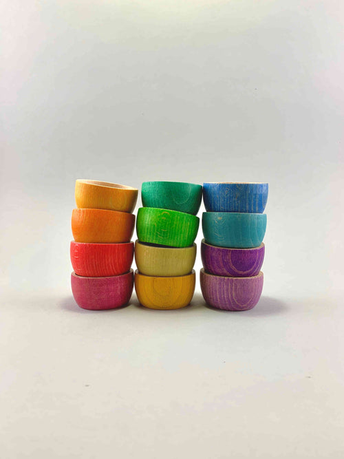 A set of 12 wooden bowls in rainbow color nested inside each other. Three stacks of 4 bowls each.