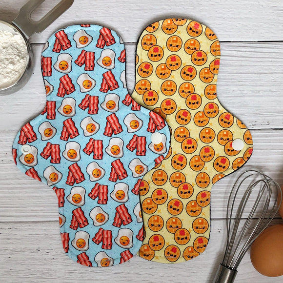 two moderate absorbency reusable pads with adorable kawaii prints in waffles and bacon and eggs