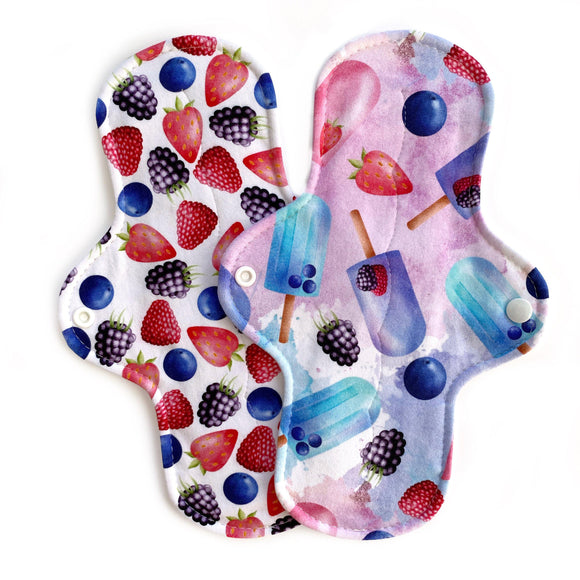 two reusable moderate absorbency cloth pads in cheerful summer prints with berries and popsicles