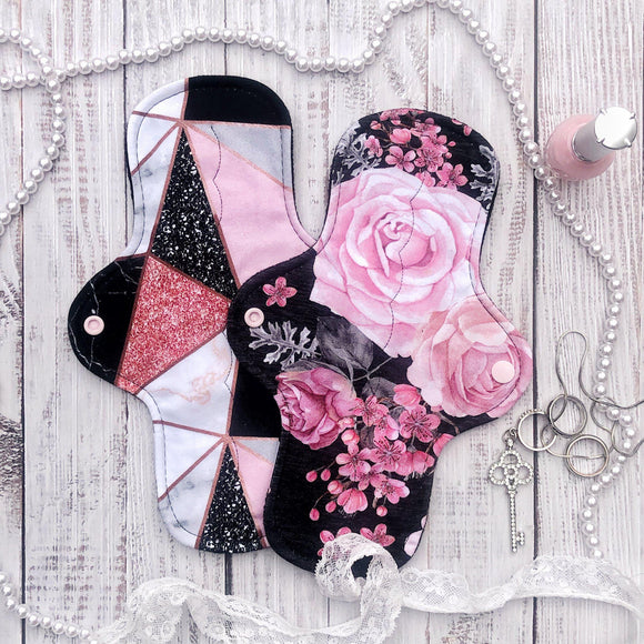 two reusable moderate absorbency cloth pads in elegant feminine prints with flowers and geometric glam