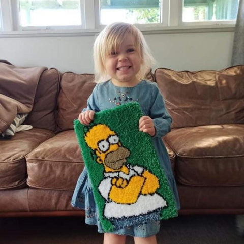 Small child holding a tufted wall hanging of Homer Simpson