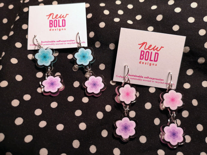 Two pairs of dangle earrings made from recycled acrylic. One pair is mint and purple flowers, the other is pink and purple flowers.