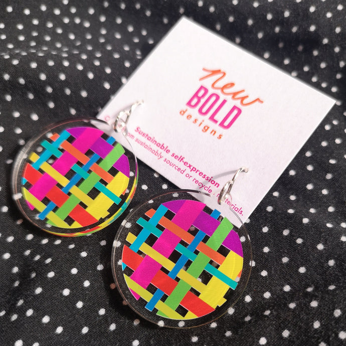 Colourful recycled acrylic earrings featuring a woven look pattern printed on a clear circular disk. Sterling silver hook tops.