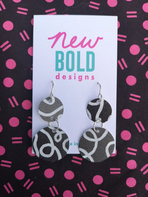 Black and white circular drop earrings. Black billboard with white curving lines. Made in New Zealand by New Bold Designs.