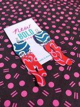 Load image into Gallery viewer, Sustainable hand painted statement dangle earrings on used billboards. Dark teal blue with white curving lines, red squiggle drops covered in pink curving lines.