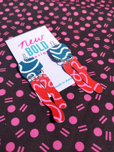 Sustainable hand painted statement dangle earrings on used billboards. Dark teal blue with white curving lines, red squiggle drops covered in pink curving lines.