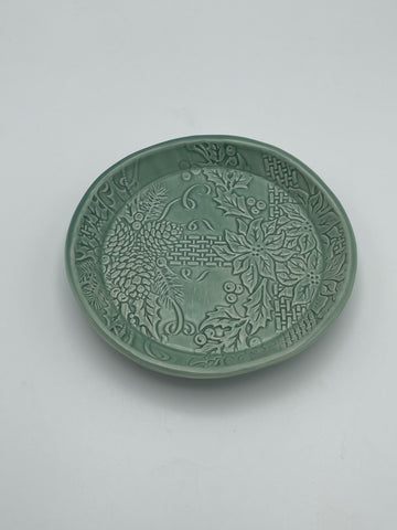 "A subtle sage green dish embossed with texture creating a pinecone, ribbon and floral motif.  This porcelain dish measures 5.5"" in diameter"