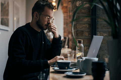 man at cafe drinking coffee and researching on computer