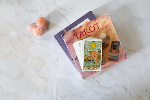 tarot cards on books with crystals
