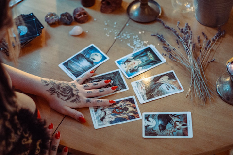 tattooed hand reading a spread of cards