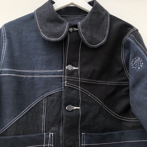 Black denim jacket with curved seam detailing and a contrasting white top stitch