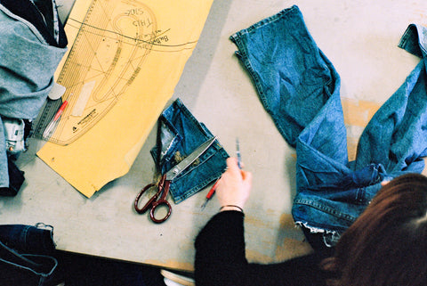 a cutting table with patterns, denim and shears.