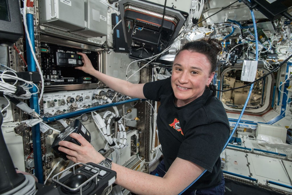 Astronaut Serena Auñón-Chancellor loading experiment modules into an MVP