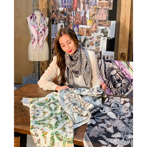 Founder and Creator of Elwyn New York, Anmy Leuthold, sitting at her desk feeling and looking at some of her scarves from her collection