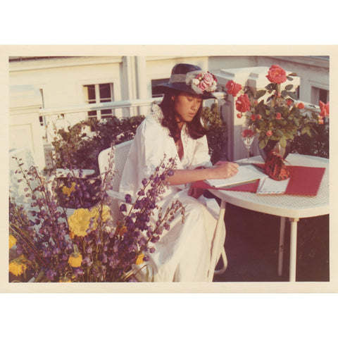 Nhumy Leuthold, Anmy Leuthold's mother wearing vintage clothes, sitting and writing amongst bouquets of flowers