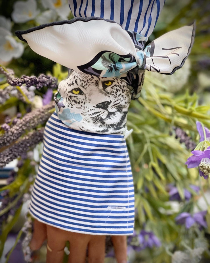 closeup of a bespoke Elwyn New York silk bandana, tied around the cuff of a sleeve with a vintage style print of a bluish floral field and modern lazing leopards