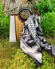 A luxury, black and white Elwyn New York silk scarf with a vintage lace print and graphic fringe border; draped through the handle of a bag that is sitting in lush grass