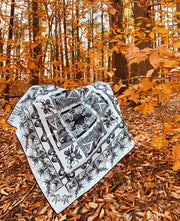 luxury, bespoke Elwyn New York silk bandana with black and white, art nouveau, whimsical, storybook print, hanging on a branch of orange fall leaves