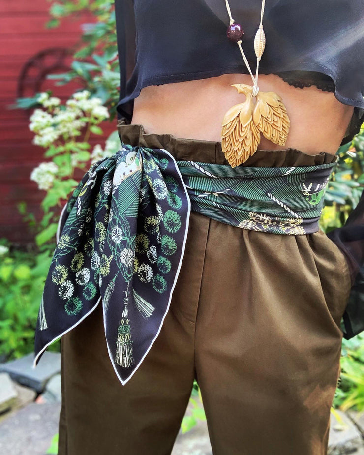 Classic woman wearing bespoke pom-pom and tassel border Elwyn New York scarf as a belt. Print has a mix of vintage entomology motifs and playful, victorian ornamental trim. Sophisticated and fun