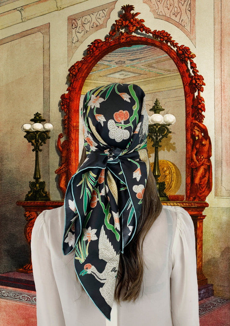Fantasy Image: Back view of a classic woman wearing bespoke Elwyn New York Scarf tied on her head with a botanical crane print is collaged together from antique glass and pearl, beaded embroideries of yesteryear. Woman is standing in front of a grand, carved ornate Mirror in a mansion