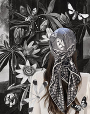 classic female surrounded by flora and butterflies wearing bespoke, luxury, black and white Elwyn New York silk scarf on her head with butterflies and vintage lace print