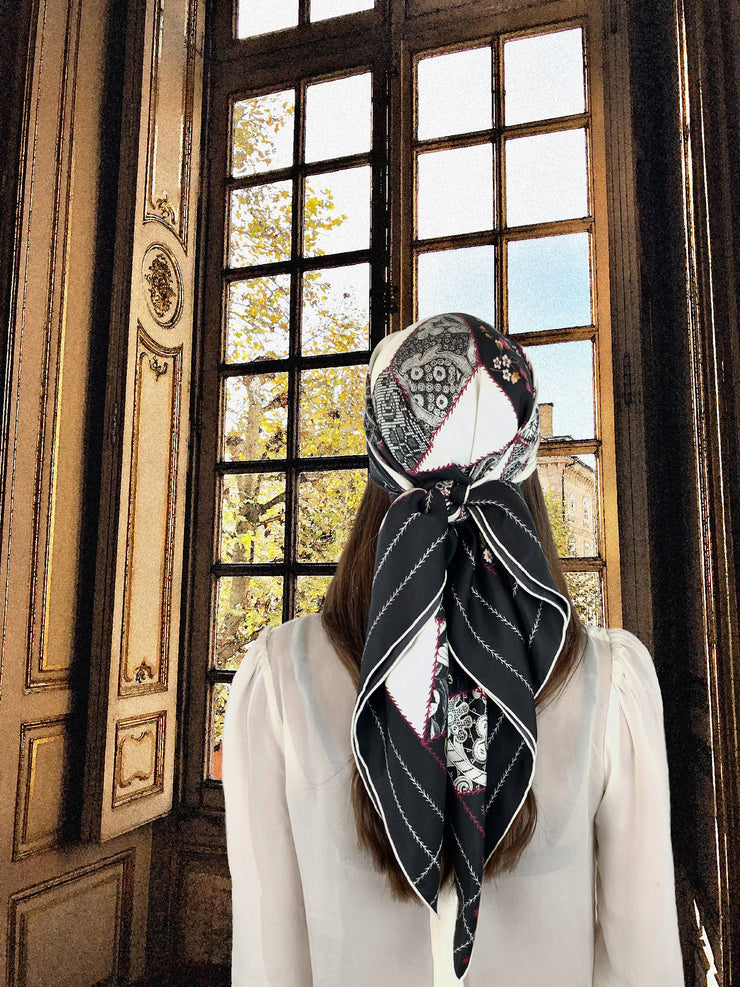 fantasy image: Back View of a classic woman wearing a bespoke, luxury Elwyn New York silk scarf. This geometric crazy quilt print is a vintage-modern depiction of the year 2020 filled with digital embroidery and lace of years past. Woman is standing in front of an ornate window looking out