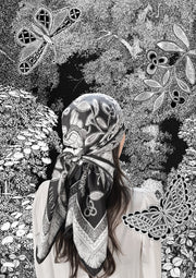 classic female traveler standing in an illustrated blooming garden, wearing bespoke, luxury, black and white Elwyn New York silk scarf on her head with vintage lace print and graphic fringe border