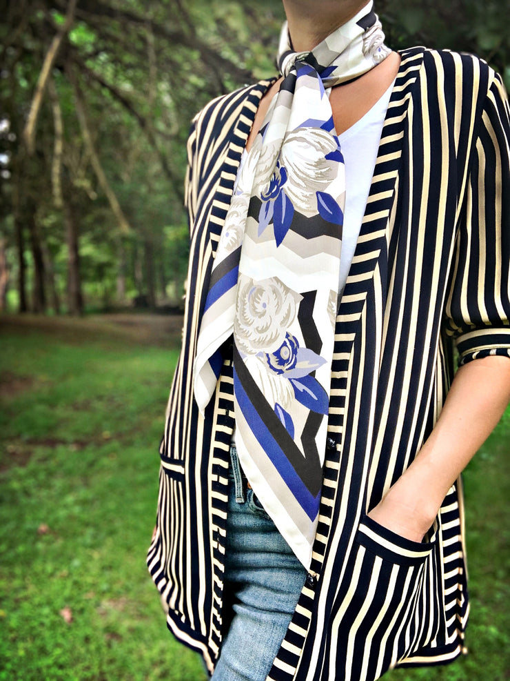 A classic woman surrounded by trees, wearing a bespoke, luxury elwyn new york scarf draped loose and long around her neck. This Denim friendly, zig-zag, art deco floral print feels modern and graphic.